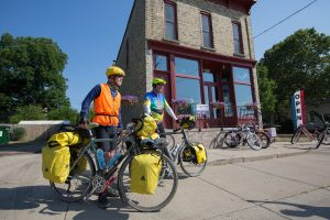 2 males dressed in bicycle gear hold bikes laden with travel packs in front of brick building with large windowed storefront