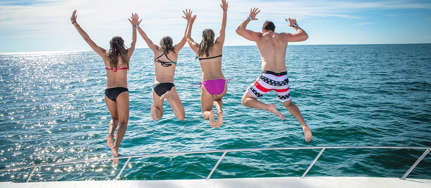 Kids jumping off boat into lake