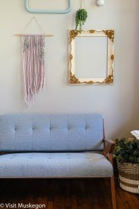 grey modern couch sits below macrame piece and empty ornate frame showcasing the decor for Depot Contemporary Inn for Visit Muskegon