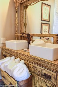 antique dresser refurbished with 2 white sinks and open drawer holding white folded towels showcasing the decor for Depot Contemporary Inn for Visit Muskegon