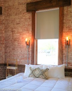 faded red brick wall and tall wood framed window set behind large bed made up with fluffy white comforter and pillows showcasing the decor for Depot Contemporary Inn for Visit Muskegon