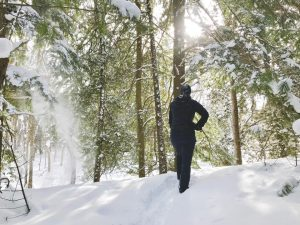 Woman in Winter attire is silhouetted with her back to the camera. She is surrounded by snow and snow covered pine trees.