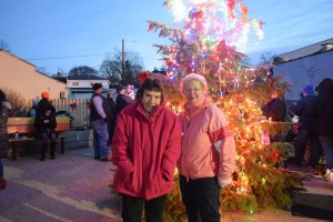 Two ladies that are sisters standing in front of the Christmas tree at the pocket park in Lakeside with the tree lit and people in the background
