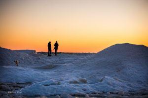 Two people standing on frozen lake or silhouetted against sunset sky of orange