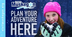 Smiling girl with pink knit hat holds pink mittens with snow in front of her face