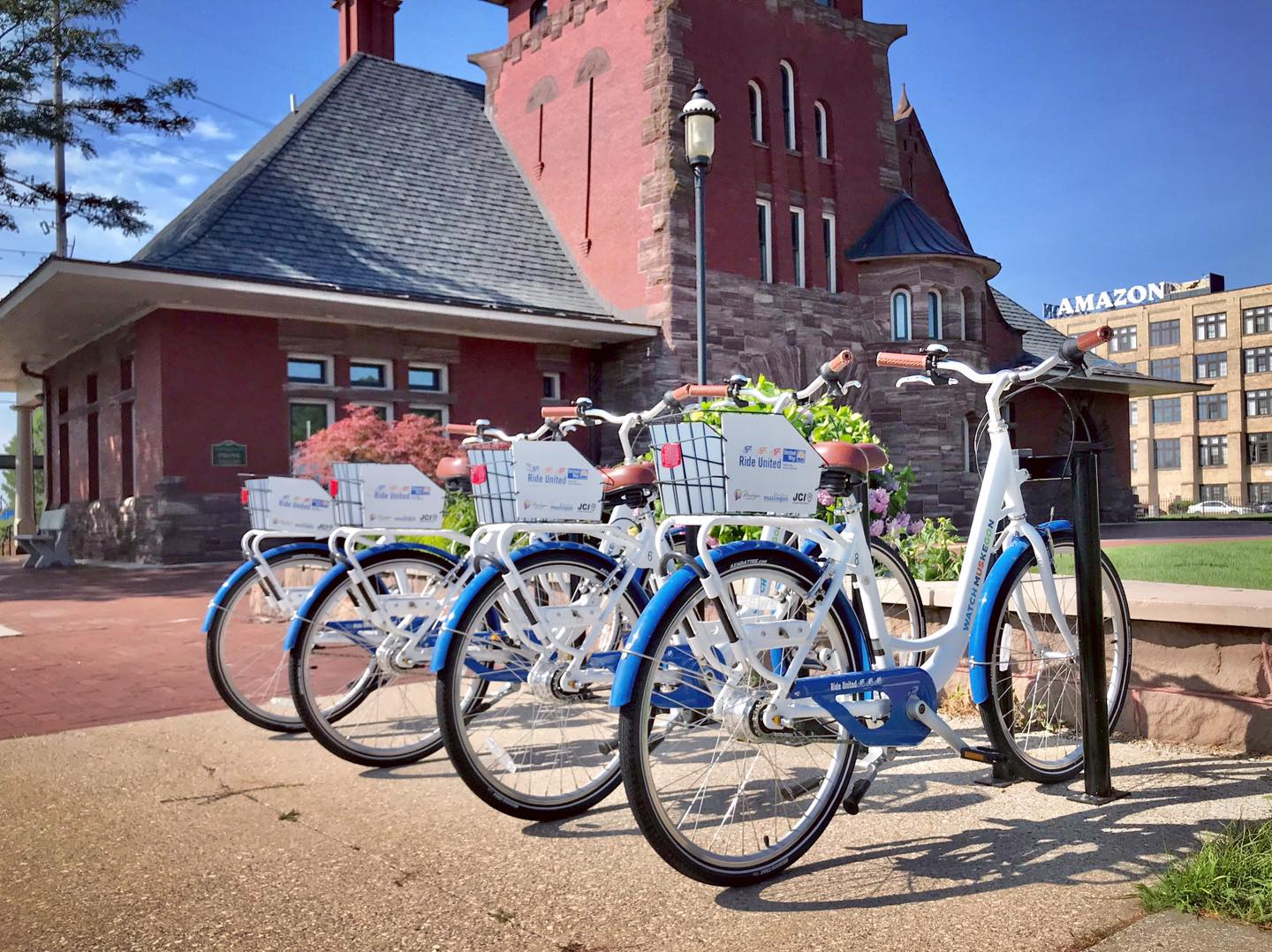 4 blue rental bikes lined up at bike rack in front of historic red brick building