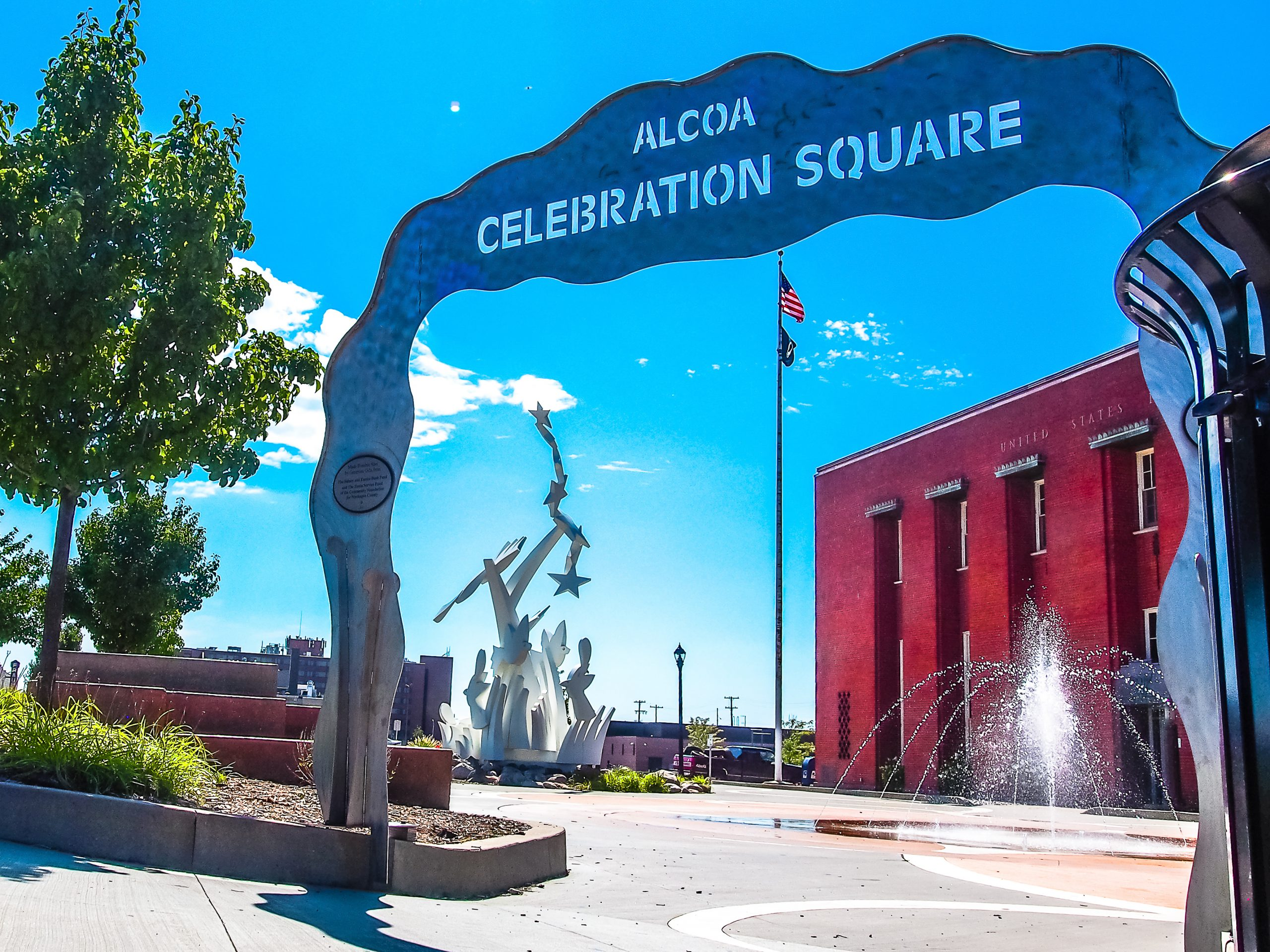Steel arch entrance with alcoa celebration squre carved at top. red brick building, fountain and white sculpture lay behind.