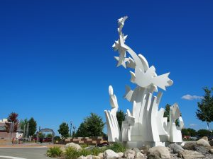 white sclulpture with stars and bird shapes is set against bright blue sky