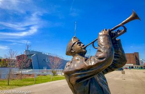 bronze sculpture of world war two soldier blowing trumpet set against blue sky. a world war two landing ship sits in the water behind