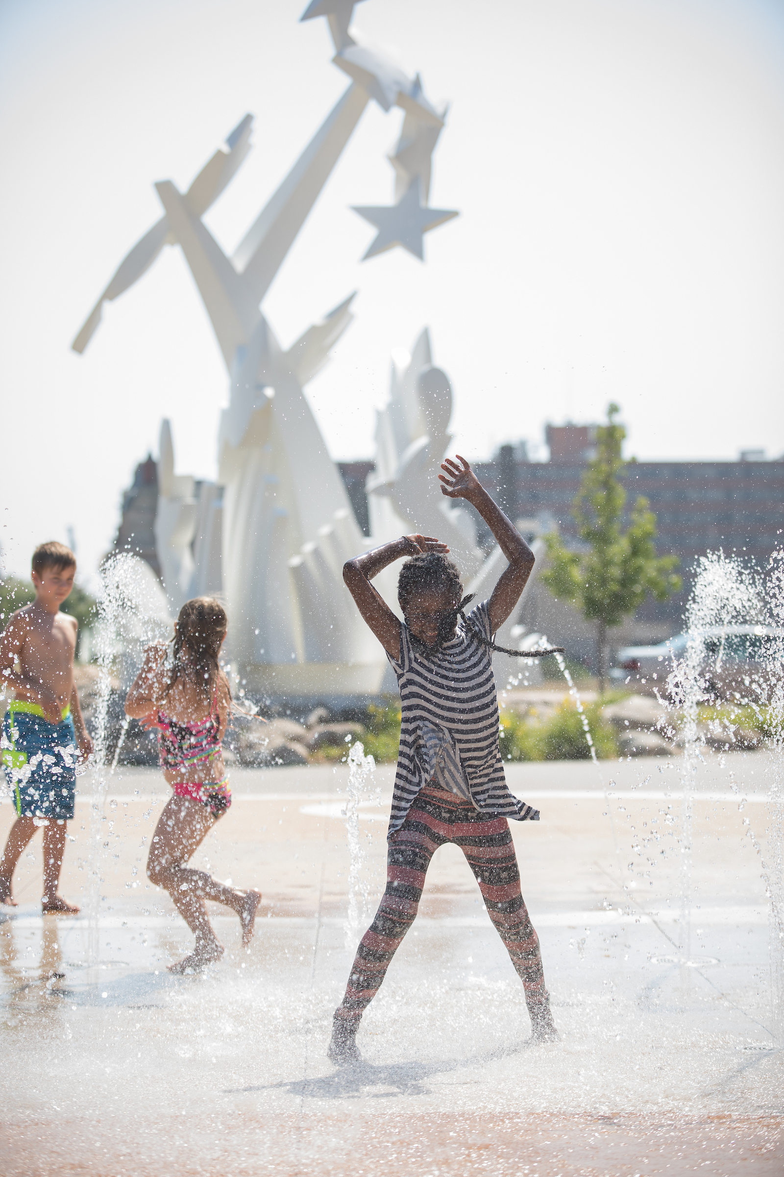 laughing girl with arms upraised plays in splash pad. white modern sculpture and playing children in background