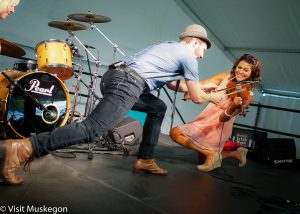 male and female musicians on stage. smiling female is on bent knees playing violin while male leans forward playing drumstick on violin