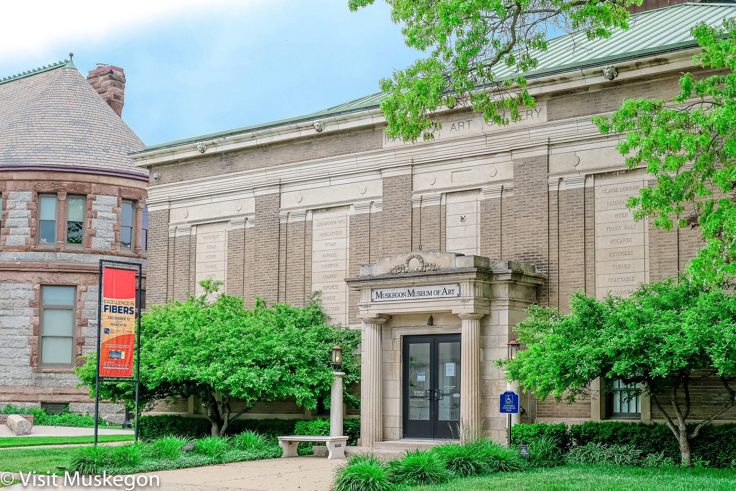 muskegon museum of art entrance; Classical Revival structure with columned portico. a bright sign sits in front with green trees.