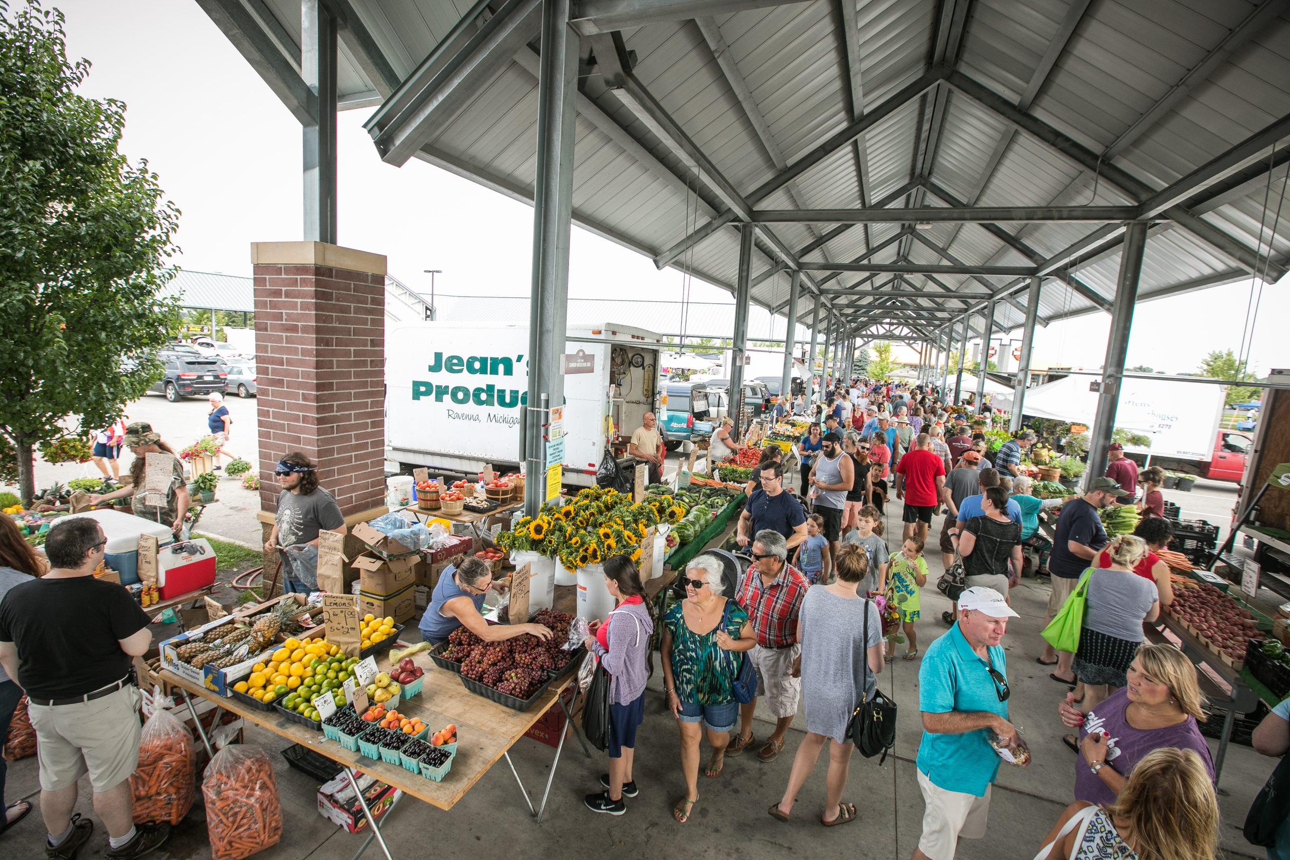 outdoor farmers market shows many shoppers on sidewalk with tables of fresh produce. a vaulted white roof covers them supported by tall white columns