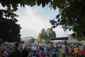 Crowd gathered in outdoor park for summer concert. trees frame photo and outdoor stage is seen in distance