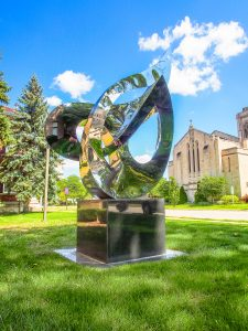 shiny, silver modern art sculpture sits on base. Green grass, blue sky and white clouds. Stone church sits to right, trees to left.