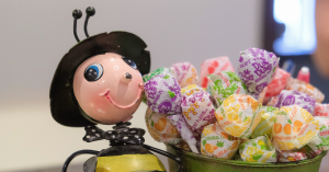 smiling bumble bee figurine next to a cup of dum dum suckers