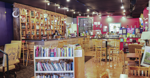 interior of book store and cafe. cart of book in foreground. cafe counter runs along side and back of photo