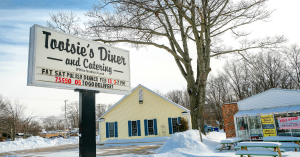 exterior winter scene of restaurant sign (tootsies diner) with large bare tree and 2 buildings.