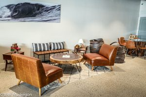 2 leather chairs and bench with striped pillows sit around round coffe table. a beachscape picture is on the wall