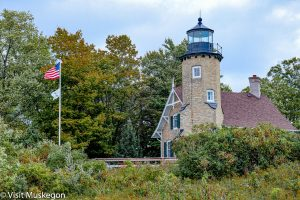 brick light house and tower sits on grassy hill surrounded by green trees. flags fly on pole in front of it. black iron clad light tops tower.