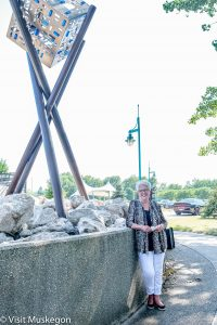 woman leans on concrete wall next to contemporary steel sculpture