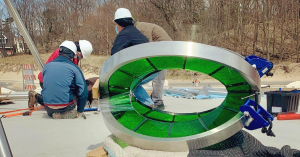 Workers installing the sculpture of steel and green glass