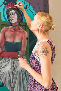 photograph of blond woman in rose dress painting a portrait of a woman