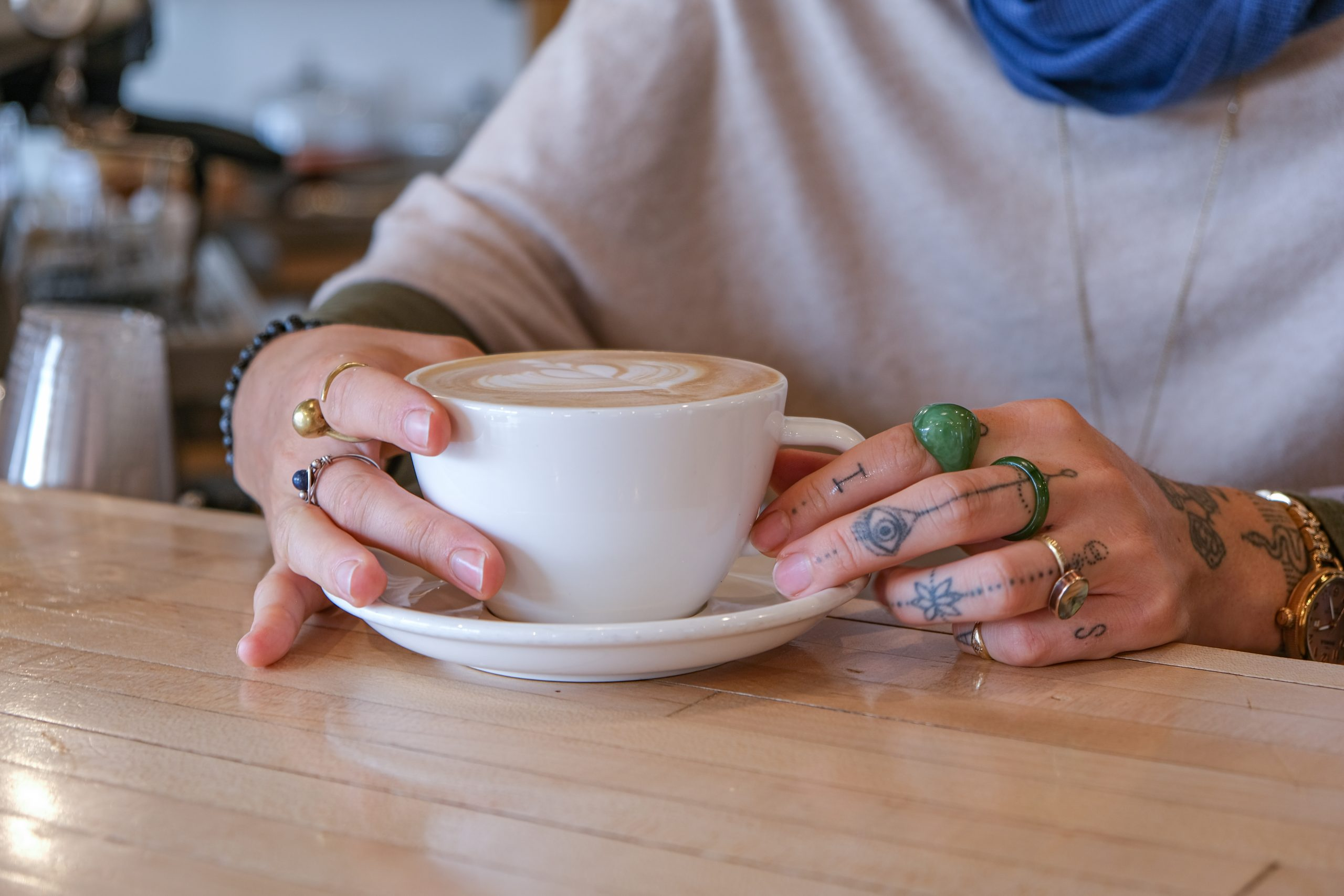 female hands with henna tatoos cradle cup of coffee