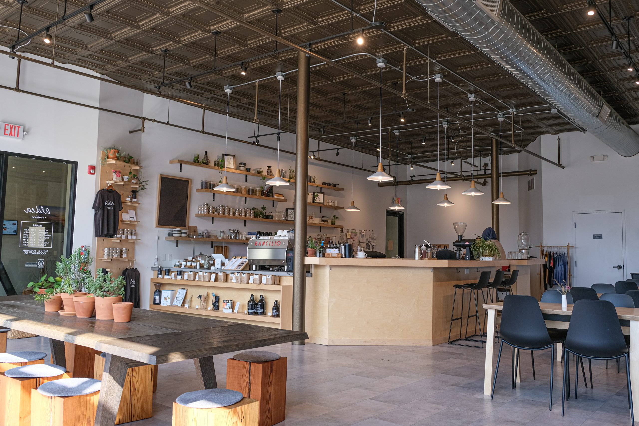 long shot of coffee shop includes light wood counter and tables